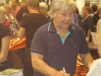 [Bild: Jan Guillou, signerar böcker.]