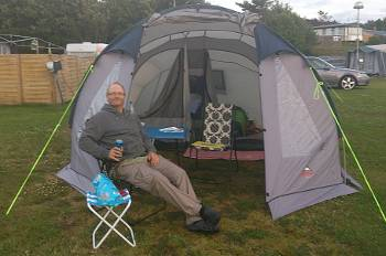 [Bild: Espeviks Camping. Nisse kopllar av utanför tältet.]